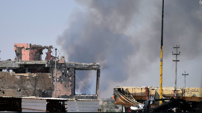 Smoke rises above a damaged building following a U.S.-led coalition airstrike against ISIS positions during a military operation to regain control of the eastern suburbs of Ramadi, Iraq, on Saturday, August 15.